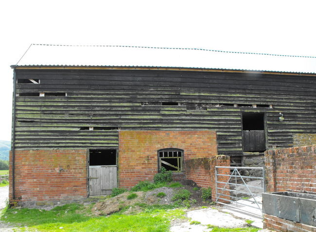 An old barn Built Structure Architecture Building Exterior Brick Wall Sky Brick Wall Day Building Entrance No People Clear Sky Wall - Building Feature Nature Outdoors Door Plant Old Abandoned House Barn Wales UK Wooden Red Brick Farm