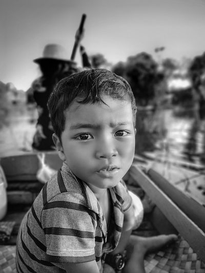 Side View Portrait Of Boy Sitting On Rowboat In River