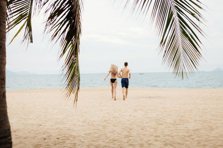 Couple walking on sand beach in Asia. Honeymoon trip. ASIA Coastline Couple EyeEm Best Shots Happiness Relationship Relaxing Resort Hotel Summertime Thailand Travel Vacations Vietnam Beach Beachphotography Honeymoon Joy Landscape Leisure Activity Relax Resort Sand Sea Summer Travel Destinations