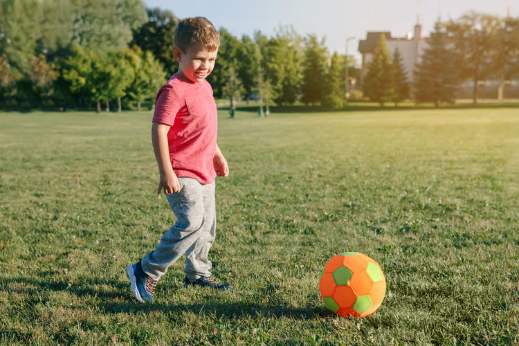 Full length of boy playing with ball on grass