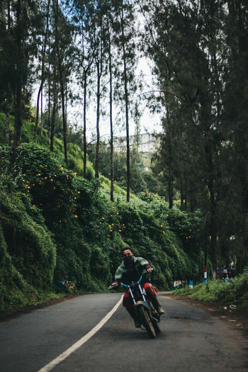 People riding motorcycle on road amidst trees in forest
