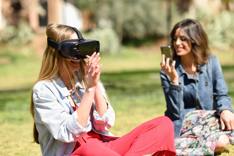 Young woman photographing mobile phone while friend wearing virtual reality simulator