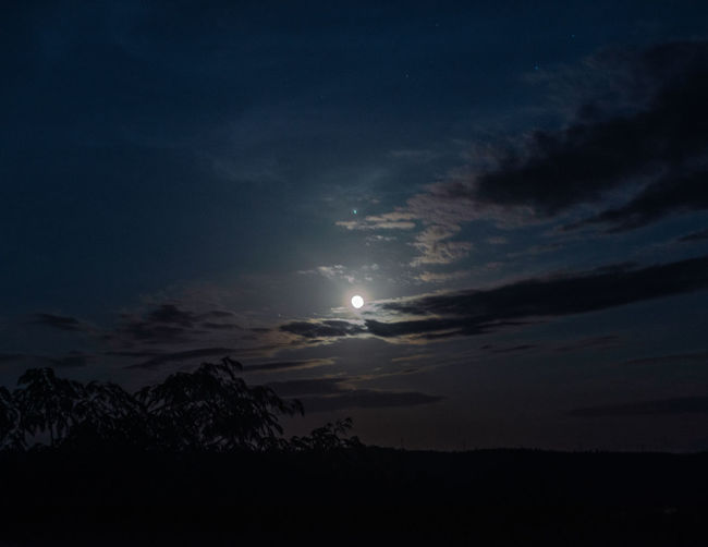 Low angle view of silhouette moon against sky at sunset