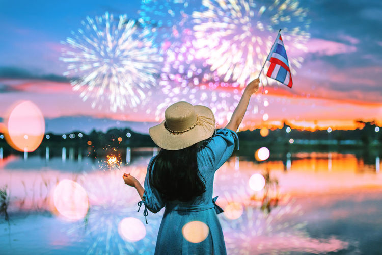 Thai National Flag Day. Celebration New Year Adult Clothing Firework Firework Display Flag Flags Flags In The Wind  Focus On Foreground Hairstyle Hat Holding Illuminated Leisure Activity Lifestyles Nature One Person Outdoors Real People Rear View Sky Standing Water Women