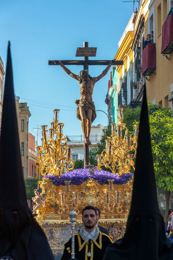 SEVILLE, SPAIN - MARCH 27: Holy Week procession with golden float with Jesus on the cross in Seville, Spain on March 27, 2018 Sevilla Seville SPAIN Day Europe European  Tourism Tourism Destination Travel Travel Destinations Easter Holy Week Semana Santa Parade Procession Black Jesus Jesus Christ People Crowd Float Nazareno Nazarenos Nazarene Nazarenes Religion Catholicism Christianity Spirituality Christian Human Representation Male Likeness