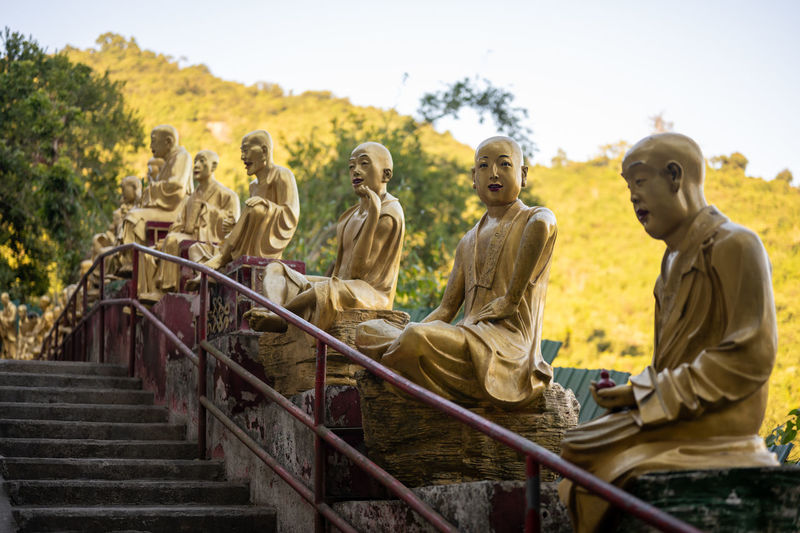 Statues sitting on staircase against sky