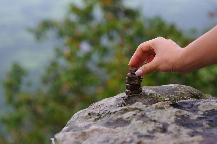 Cropped hand of woman stacking rocks in forest