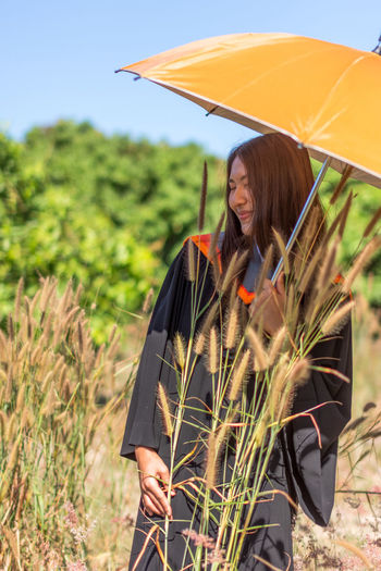 Smiling Young Woman With Umbrella Standing On Field