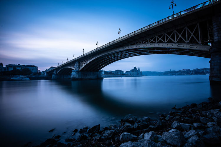 Copy Space Architecture River Water Nature City Morning Sunrise Sky Bridge Blue Morning Light Dawn Outdoors Transportation Waterfront Overcast Connection Arch Bridge Built Structure Bridge - Man Made Structure Arch Engineering Low Angle View Long Exposure