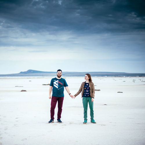 Portrait of young couple standing on beach against sky