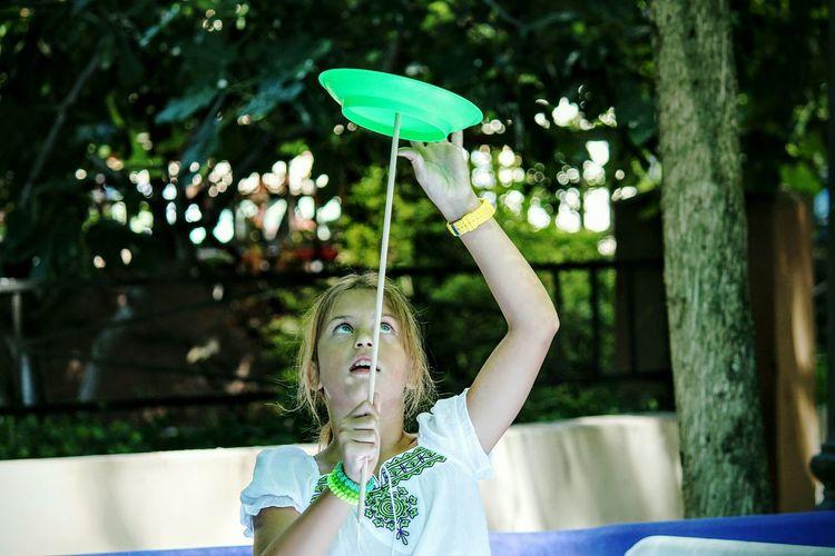Girl Balancing Plate On Stick And Playing