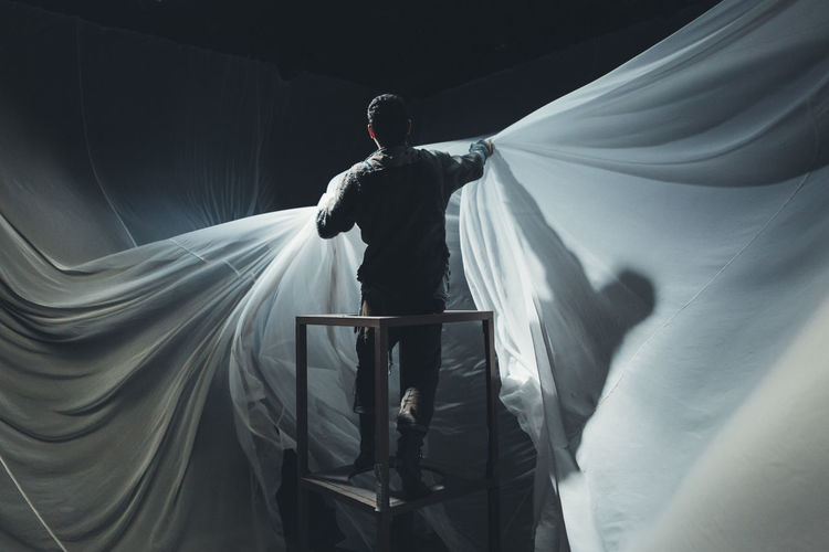Man rehearsing with curtain at stage theater