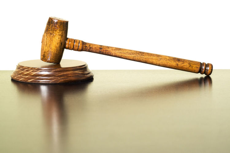 High angle view of gavel on wooden table against white background