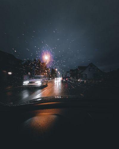 Illuminated city seen through wet windshield during rainy season