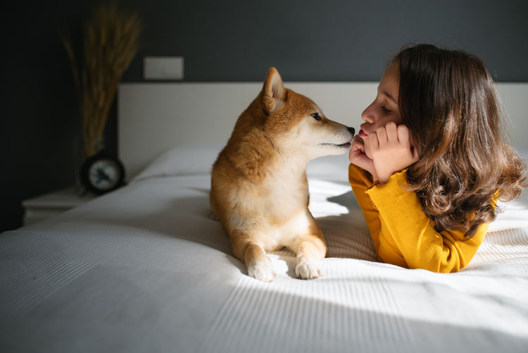 Woman with cat on bed at home