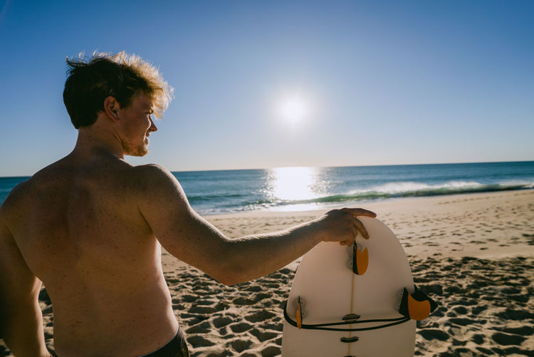 Rear View Of Shirtless Man With Surfboard At Beach During Sunset