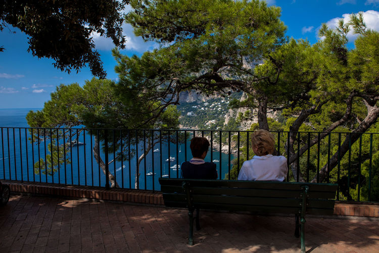 Capri, Italy, two ladies sitting on a bench enjoy the view over the sea taken from Punta Tragara, one of the most scenic points of the island. Beauty In Nature Bench Bench Capri Holiday Italy Nature Panorama Panoramic People Relaxation Relaxing Scenery Scenic View Sea Sea And Sky Sitting Sky And Sea Tranquil Scene Tranquility Traveling Tree Tree Vacations