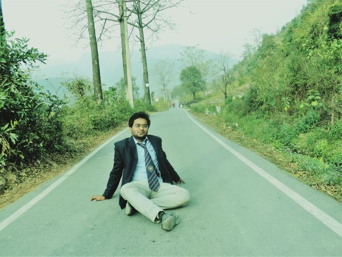 Portrait of young man sitting on road against trees