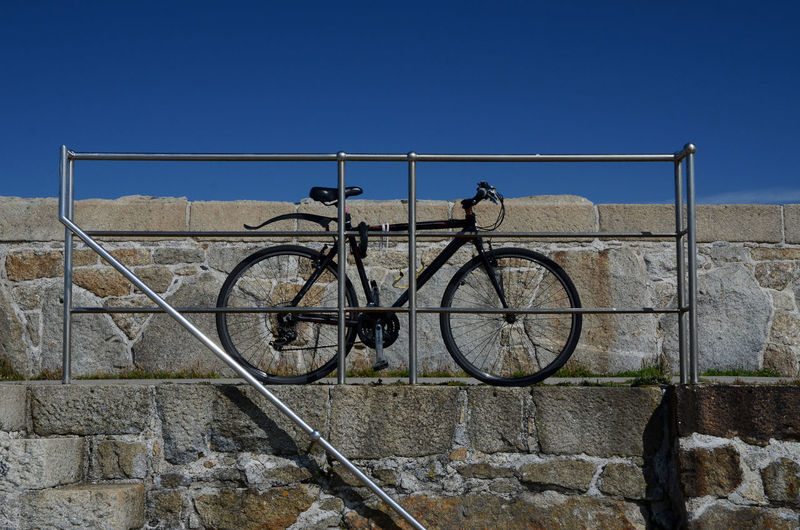 Low angle view of bicycle parked by railing on footpath