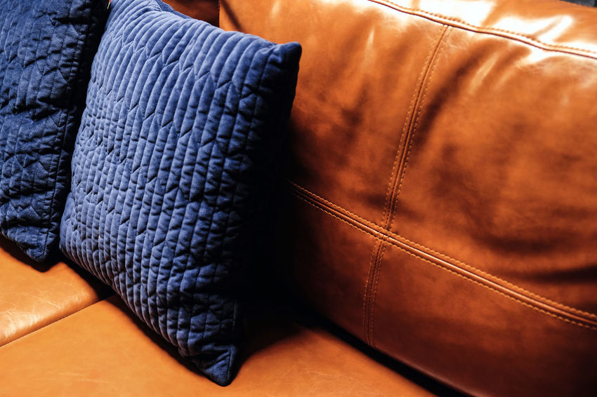 Close up detail of blue pillow on leather sofa Decor Interior Decorating Pillow Absence Brown Close-up Clothing Cushions  Decoration Fashion Furniture Home Interior Indoors  Jeans Leather Leather Sofa Lifestyles Luxury No People Orange Color Pillow Relaxation Seat Single Object Sofa Still Life Textile
