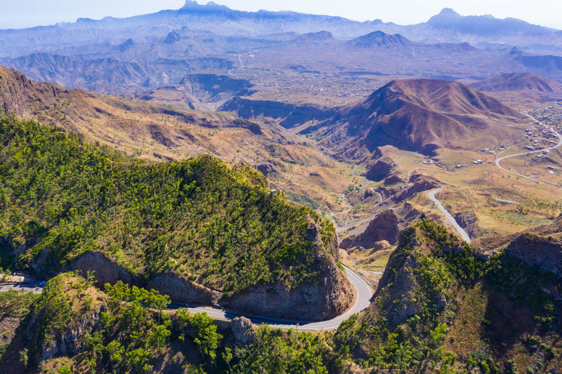 Aerial view of road amidst trees and mountains