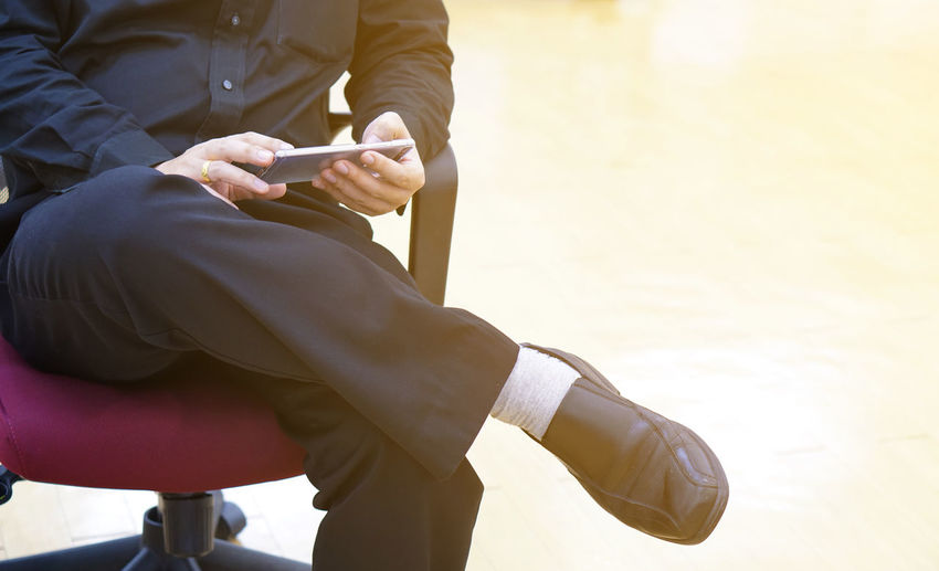 Low section of mobile phone using mobile phone while sitting on chair