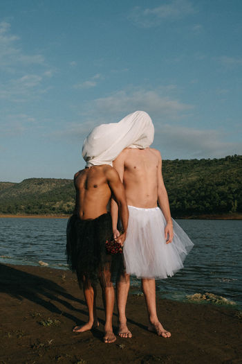 Shirtless gay couple wearing skirts while standing against lake