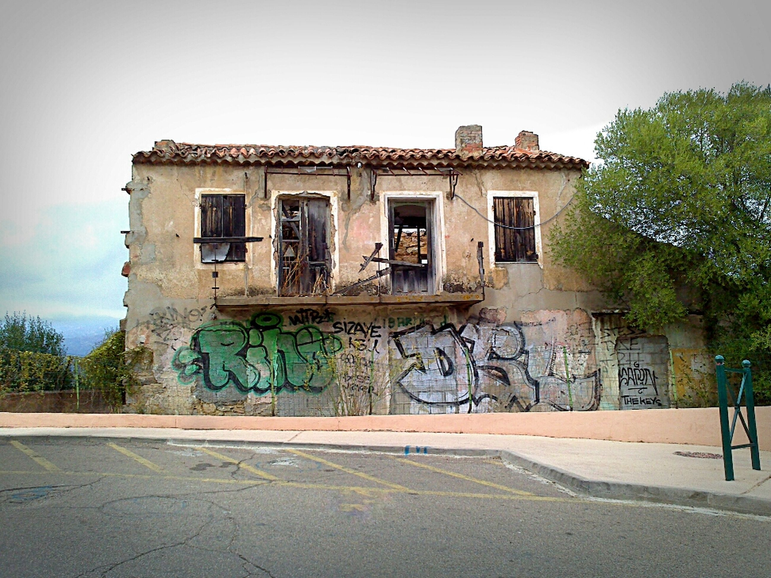 architecture, building exterior, built structure, graffiti, wall - building feature, window, house, day, sky, art, clear sky, art and craft, outdoors, street, facade, wall, building, tree, no people, residential structure