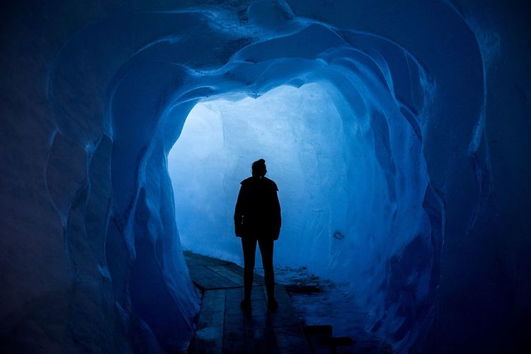 silhouette of a girl in a tunnel of ice Climate Change Climate Nachhaltigkeit Future Cold Tunnel Ice Cave Eis Ice Glacier Silhouette Standing One Person Full Length Rear View Men Night Nature Blue Mystery Outdoors