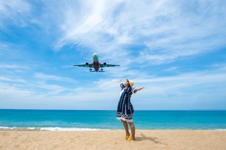 Woman standing below flying airplane at beach against sky