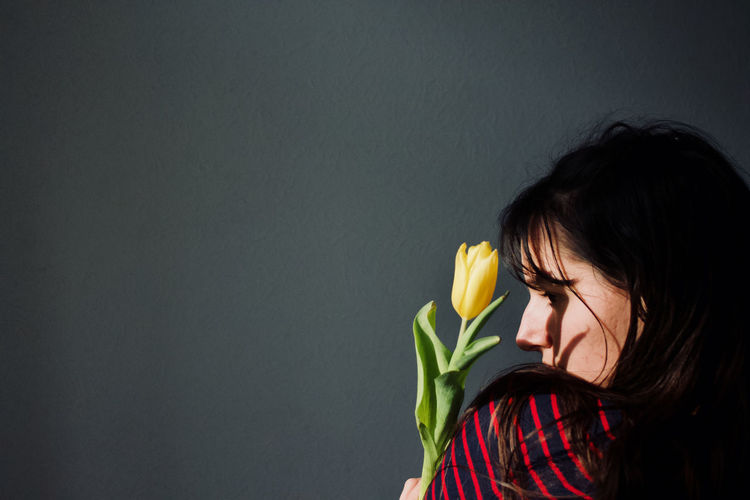 Woman holding flower against gray wall