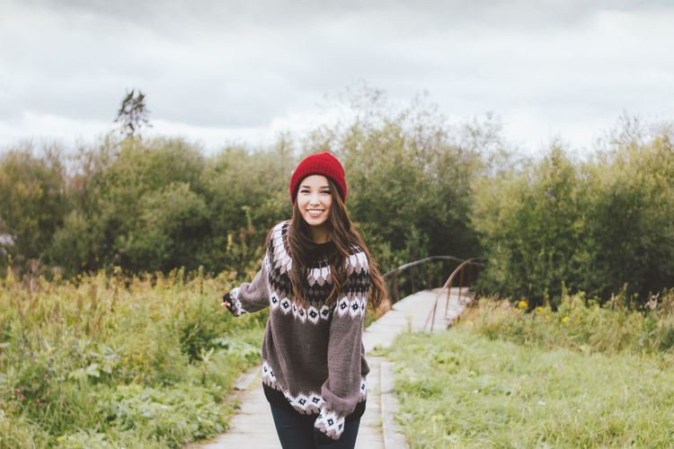 Portrait of smiling young woman standing on footpath against trees and plants