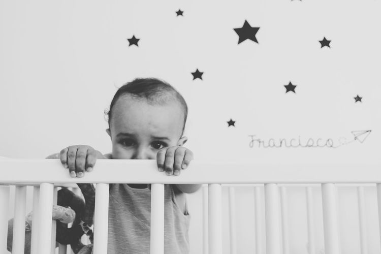 Portrait of baby boy in crib