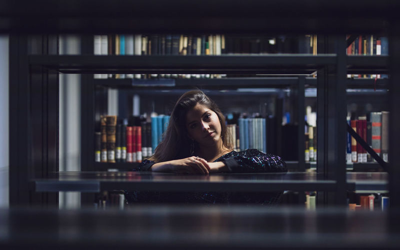 Portrait of young woman seen through bookshelves at library