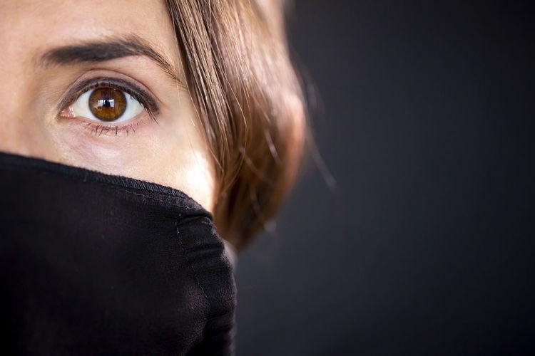 Portrait of woman against black background