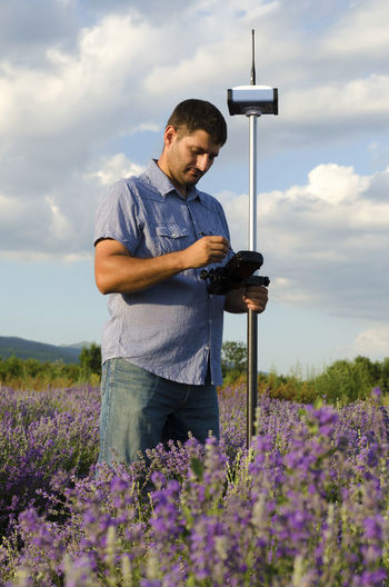Surveyor using equipment on lavender field against cloudy sky