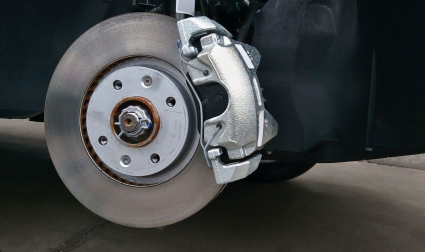 Close-up of a disc brake with caliper during tyre replacement. Car maintenance. Automobile Mechanic Repairs Service Auto Automotive Break Caliper Car Close-up Disc Disc Break Maintenance Metal No People Pad Part Repair Replacement Tire Tyre Vehicle Vehicle Part Wheel