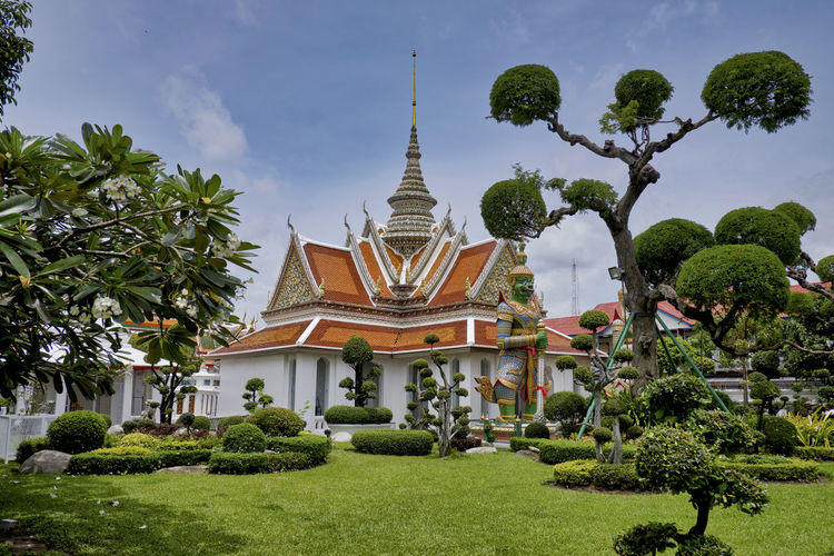 A temple at Wat Arun Architecture Plant Built Structure Tree Building Building Exterior Religion Place Of Worship Belief Sky Nature Growth Spirituality Green Color Travel Destinations Day No People Outdoors Spire  Hedge