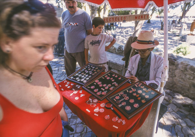 Jun 2001 - Coin vendor in the Castle of São Jorge City Of Seven Hills Hat Day Hot Day Lisboa Portugal Open Shade Red Street Life Adult Casual Clothing Clothing Coins On The Table Day Destination Front View Group Of People Lifestyles Males  Men Portrait Real People Standing Tourist Destination Waist Up Women