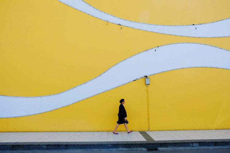Side view of people walking on yellow wall