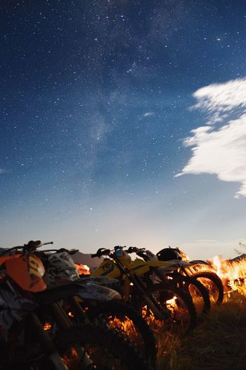 Motorbikes parked on field against sky at night