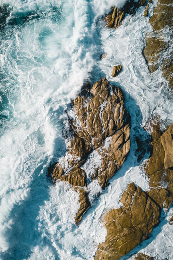 Aerial image of waves hitting the coastline of the french island corse near the village lumio.