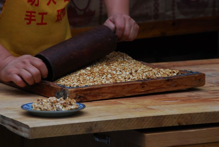 Midsection of chef crushing caramel on wood at street market stall