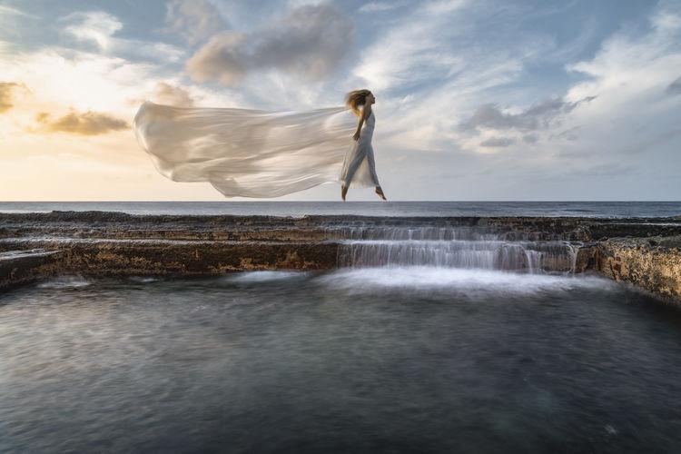 Female dancer jumping on seawall during sunset