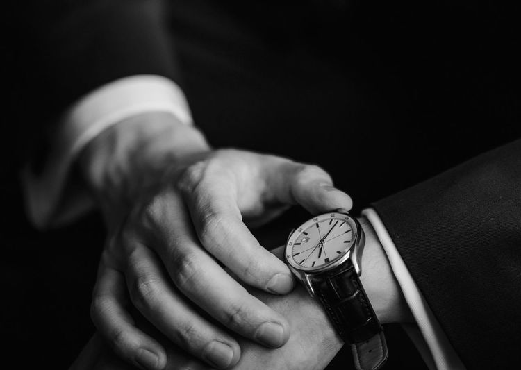 Closeup of businessman checking time on watch