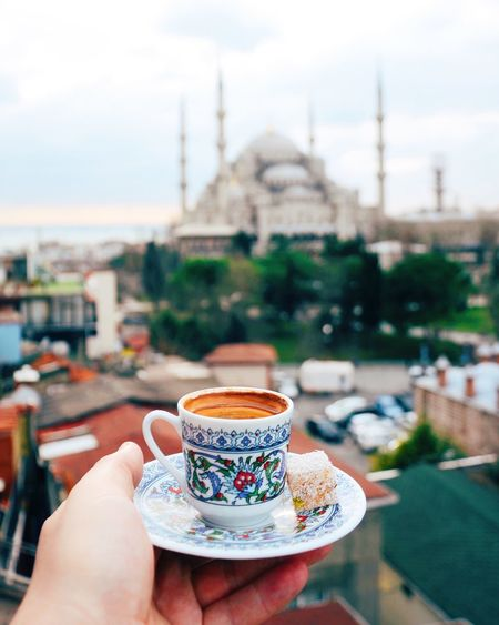 Cropped Hand Holding Tea Cup Against Sultan Ahmed Mosque In City