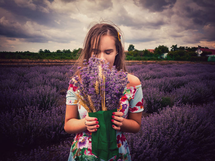 Woman smelling lavender flowers while standing on field against sky