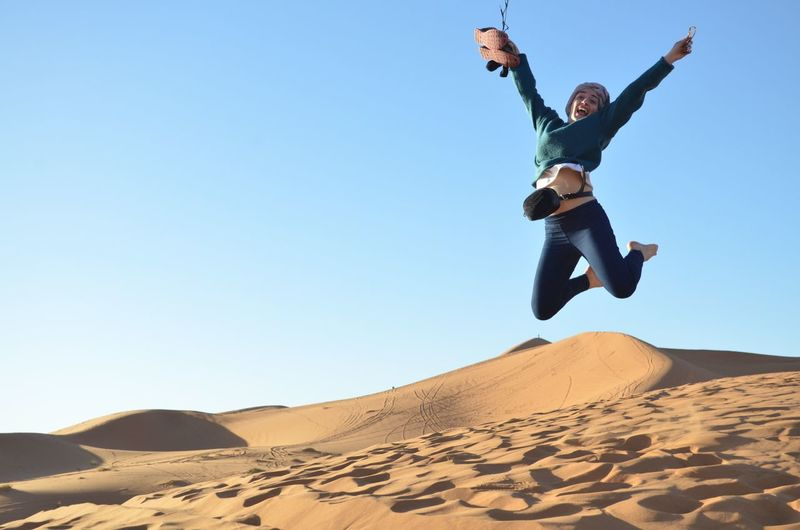 Full length of excited young woman jumping in desert against clear sky