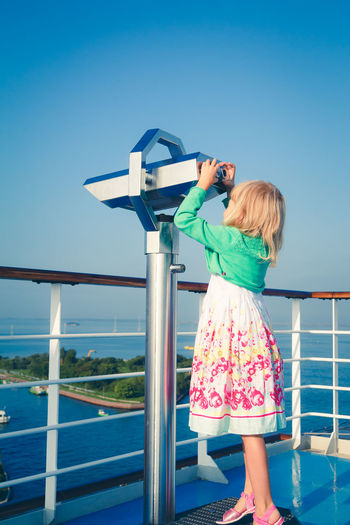 Girl standing by coin operated binoculars against sky
