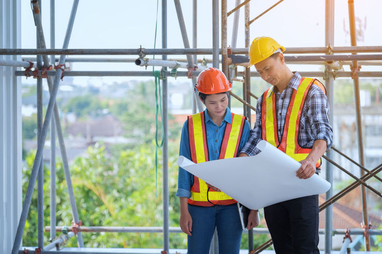 Coworkers Looking In Blueprint While Working At Construction Site